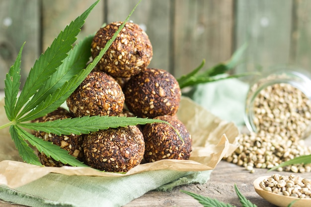 グラノーラ、プルーン、ナッツ、エンバク、ナツメヤシで調理した食欲をそそるエネルギーボールと大麻の種子と緑の葉。
