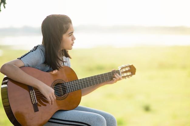 Милая девушка играет на гитаре