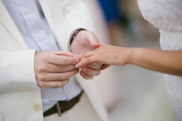結婚指輪を持つ花嫁と新郎の手