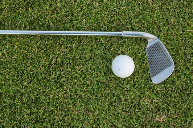 芝生のゴルフボールとゴルフクラブ