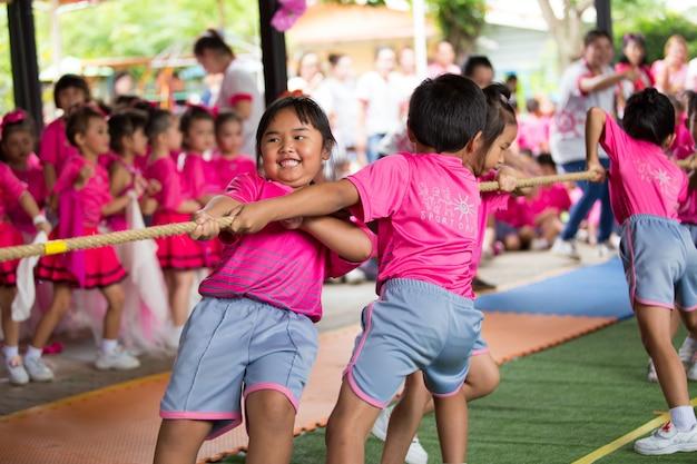 遊び場で綱引きを遊んで幸せな学校の子供たちの多民族グループの正面図