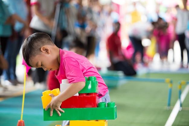Маленький азиатский ребенок играя с красочными строительными блоками