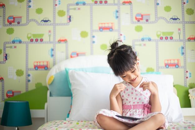 彼女の装飾された寝室のベッドの上でスマートフォンで音楽を聴くためにヘッドフォンを使用しているアジアの子供たち