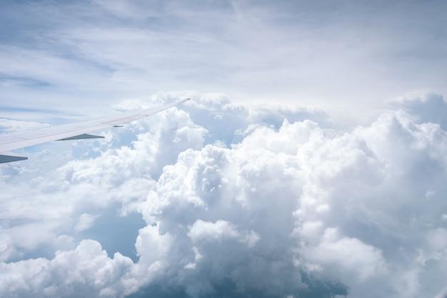 ウインドウを通して青空の背景に雲の上を飛んで飛行機の翼。