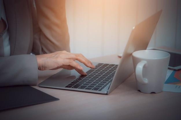 ビジネスの女性は、オフィスでノートパソコンと白いコーヒーカップを使用します。ビンテージトーン