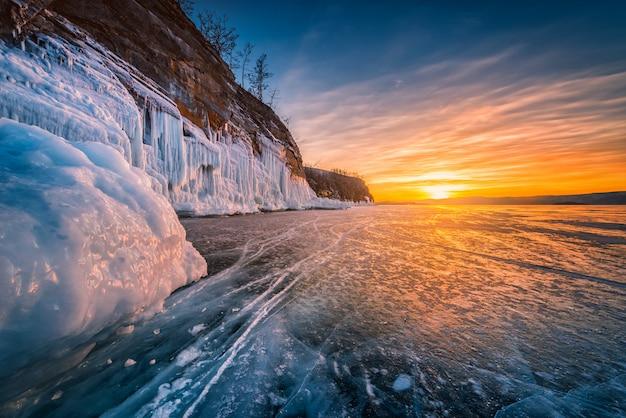 ロシア、シベリアのバイカル湖の凍った水の上の自然な砕氷と夕焼け空。