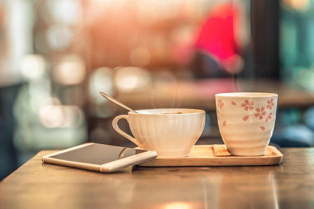 コーヒーショップで木製のテーブルの上のスマートフォンとホットコーヒーグラスカップ。ビンテージトーン