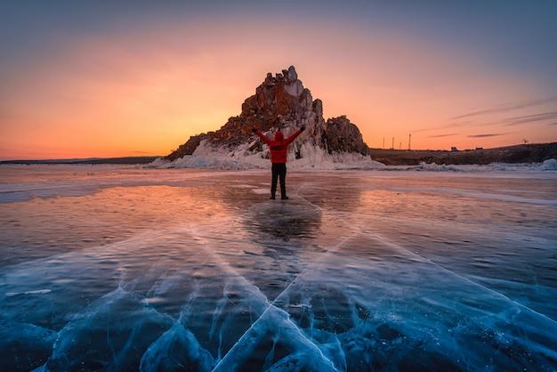 旅行者の男は赤い服を着て、バイカル湖、シベリア、ロシアの日の出で凍った水の自然な砕氷の上に立って腕を上げます。