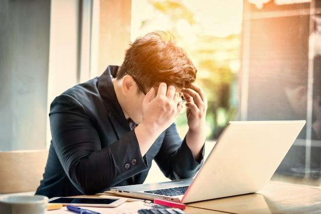 Сад бизнесмен подчеркнул и беспокоился, сидя в офисе. концепция стресса и беспокойства. винтажный тон