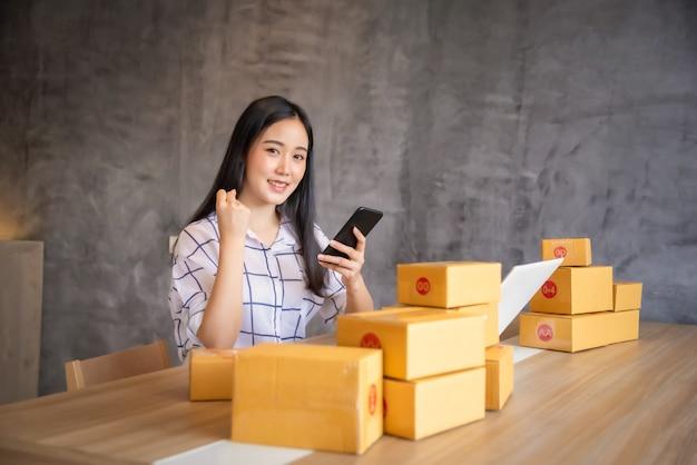 Портрет покупок молодых азиатских работая онлайн с портативным компьютером дома. продажа онлайн и концепция доставки