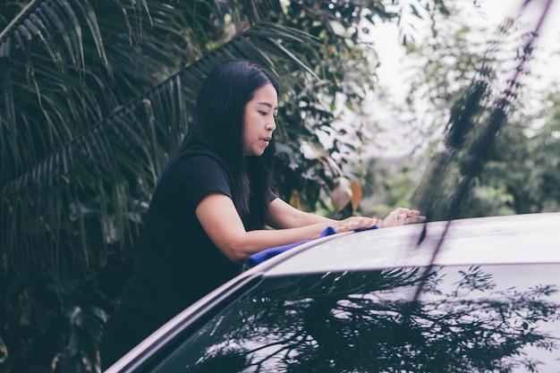マイクロファイバー布で車の屋根を洗うアジアの女性。