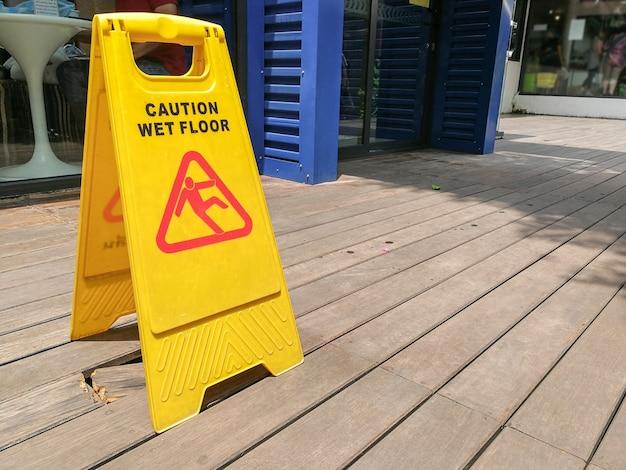 注意湿った床の警告標識は木製の床にぼやけている。