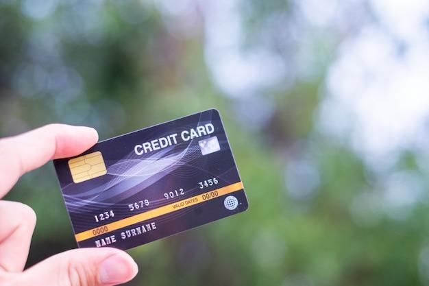 男性はボケ味にクレジットカードを保持します
