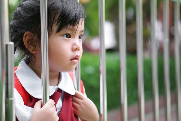 アジアの女子学生が学校の制服を着て学校に行き、ステンレス鋼のフェンスを保持