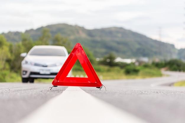 道路上の赤い緊急停止標識と壊れた銀の車
