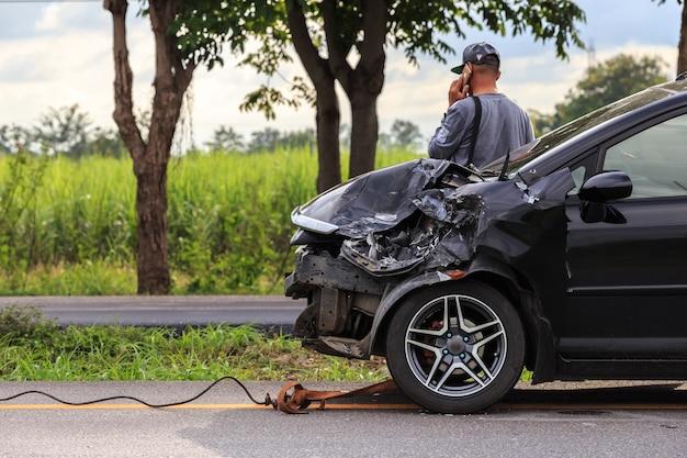 黒い車の前が道路上の事故によって損なわれる