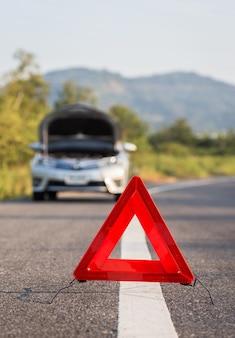 Красный знак аварийной остановки и сломанный серебряный автомобиль на дороге