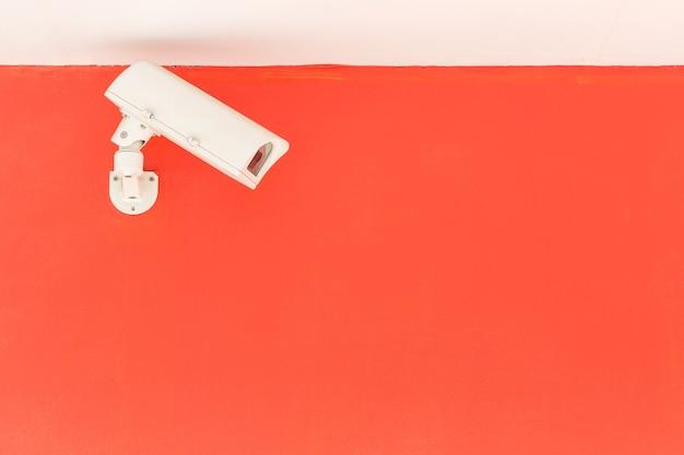 Белая камера видеонаблюдения, работающая на красной стене здания