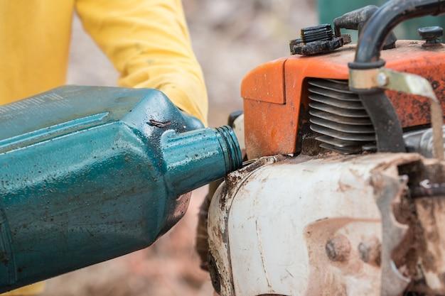 電動工具のエンジンにオイルを充填するタイの労働者