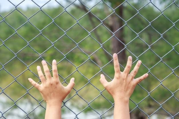 Закройте руки, висящие на металлическом зацеплении звеньев цепи