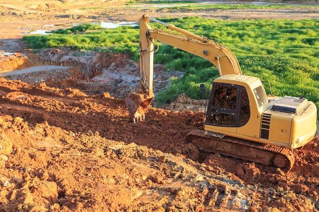 掘削機の掘削と地球の除去。掘削機は地面を調整する