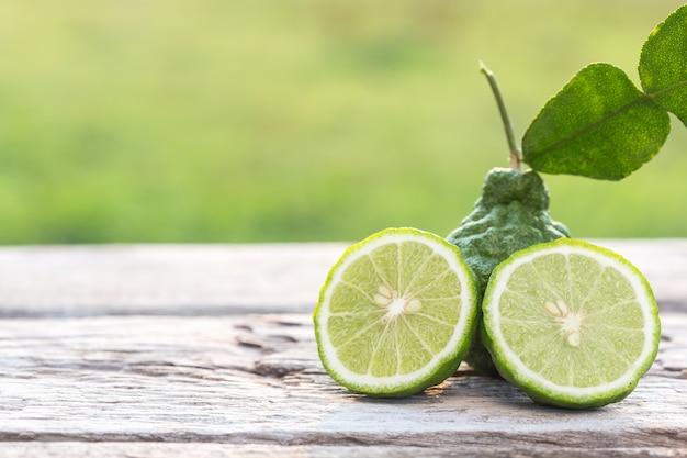 木製のテーブルの背景にスライスグリーン新鮮なベルガモットの果実を閉じます