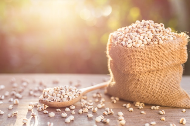 Закройте рис проса или зерна проса в маленьком мешке на деревянном столе