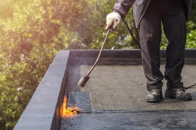 Азиатский рабочий, устанавливающий смоляную фольгу на крыше