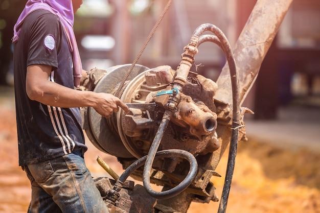 Азиатский рабочий, устанавливающий кукурузную груду для наружного общественного строительства
