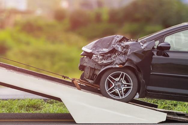 黒い車の前が道路上の事故によって損傷を受ける。
