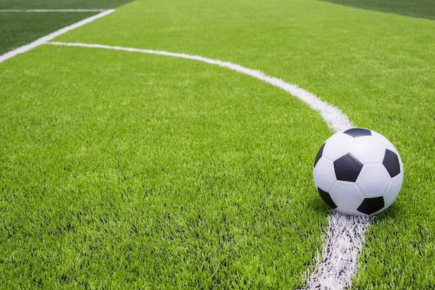 人工的な明るく暗い緑の草の古典的なサッカーボール
