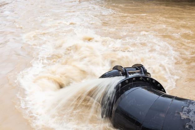 Черная большая водопроводная труба при перекачке воды в реку