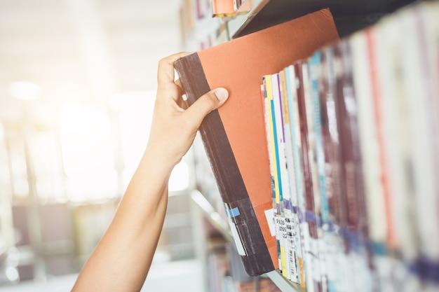 Женщина держит и читает книгу в комнате публичной библиотеки. концепция образования.