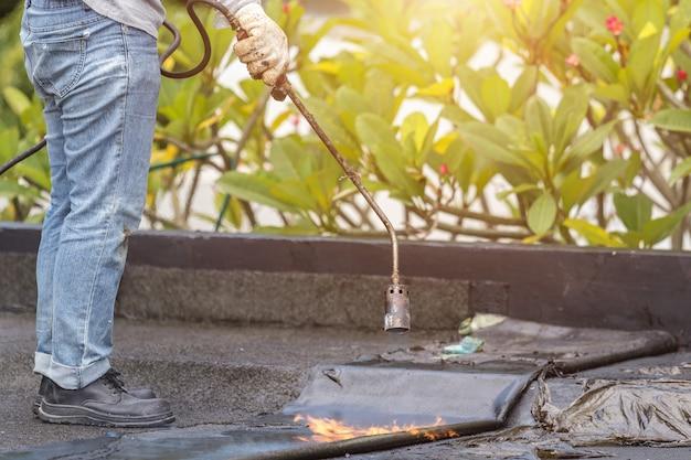 ビルの屋上にタール箔を取り付けるアジアの労働者。