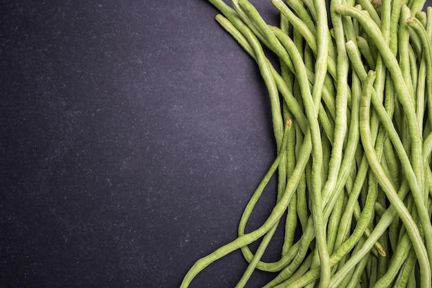 トップビュー新鮮な緑のササゲまたはアスパラガス豆の黒い石