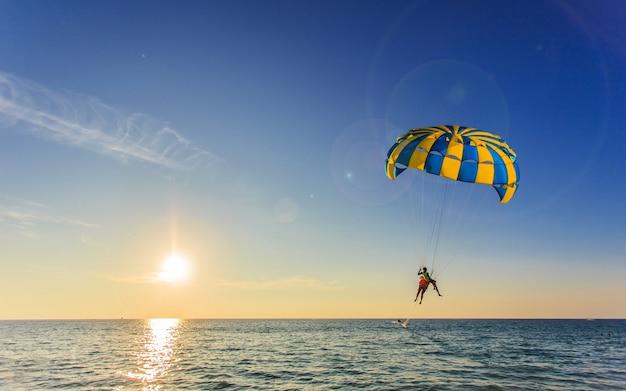 Турист находится под парусом над синим морем во время заката в таиланде
