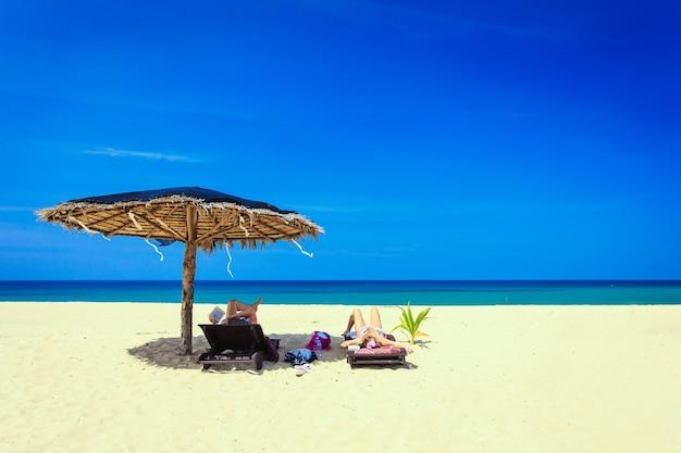 青い空の日に白い砂浜で太陽の傘とサンベッドの観光客