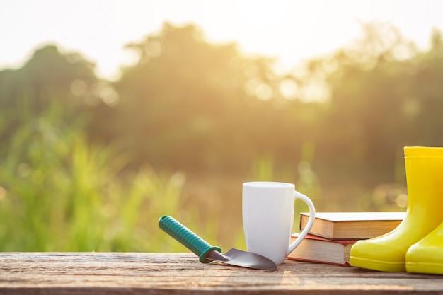 朝の時間で日光の木製テーブルにコーヒー、本、庭の機器のカップ