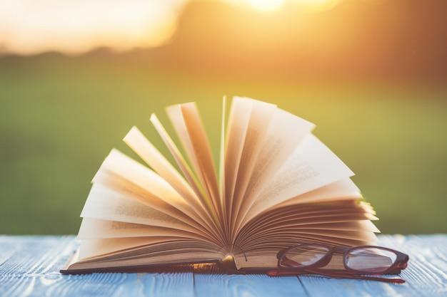 日の出や日没の時間に抽象的なぼかしとボケと木製のテーブルに本と眼鏡