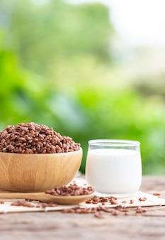 朝食シリアル、ココアをボウルに入れ、牛乳のガラスを木製テーブルに盛ったパフスリード