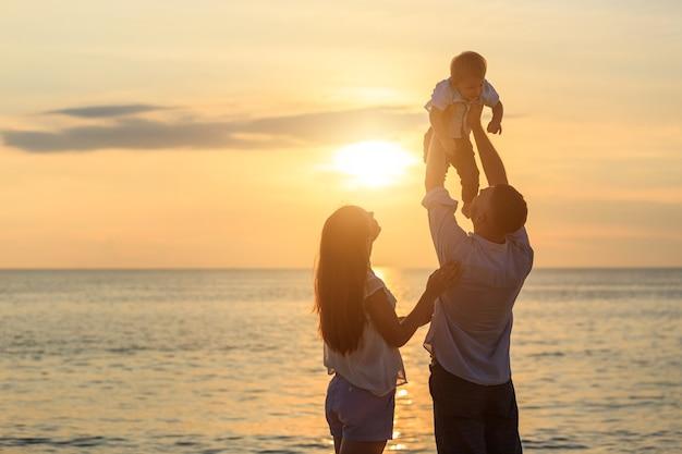ビーチコンセプトの家族、熱帯砂浜で遊んで息子を運ぶ父