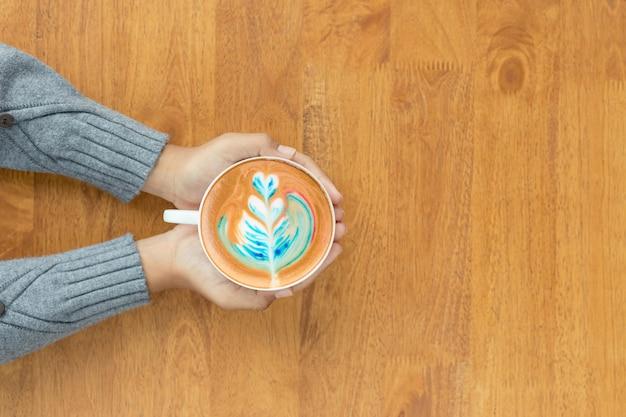 Рука чашку горячего кофе латте арт в кафе.