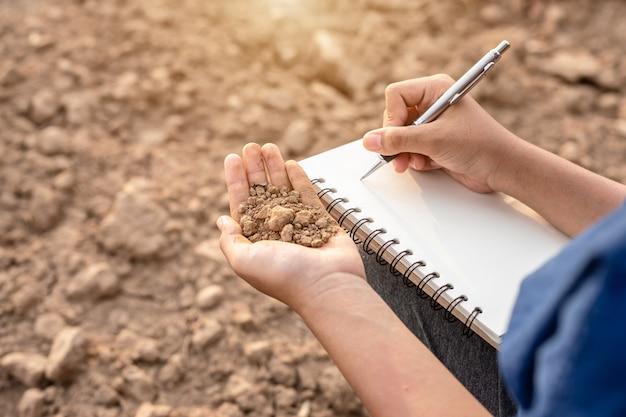アジアの学生が植栽のための研究を行うか、空地の乾燥土壌をチェック
