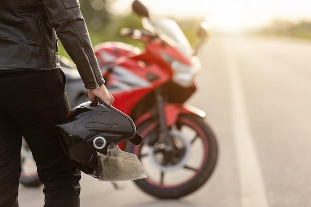 Красивый мотоциклист носит кожаную куртку, держа шлем на дороге