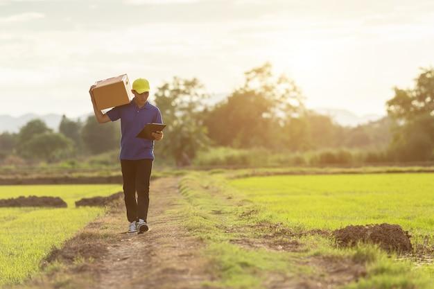 配達人の田舎で顧客への茶色の小包または段ボール箱の配達を保持