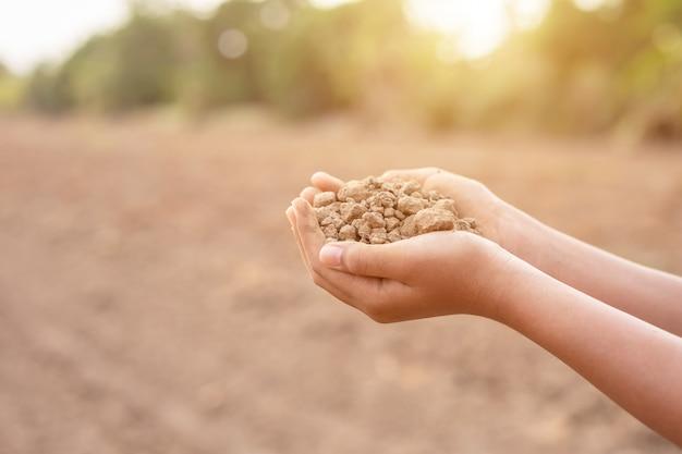 植栽のための空の土地で乾いた土壌を保持している若い農家