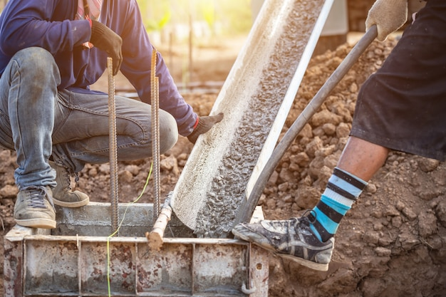 Заливка бетона в стальную коробку для фундамента в процессе строительства дома