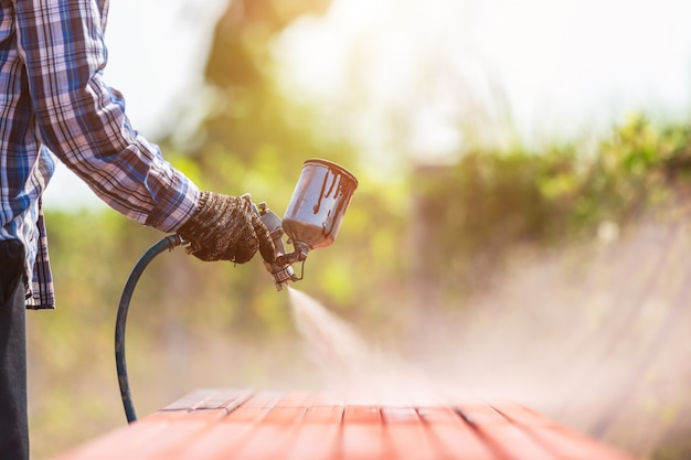 表面の錆を防ぐために鋼管に塗料をスプレーする労働者