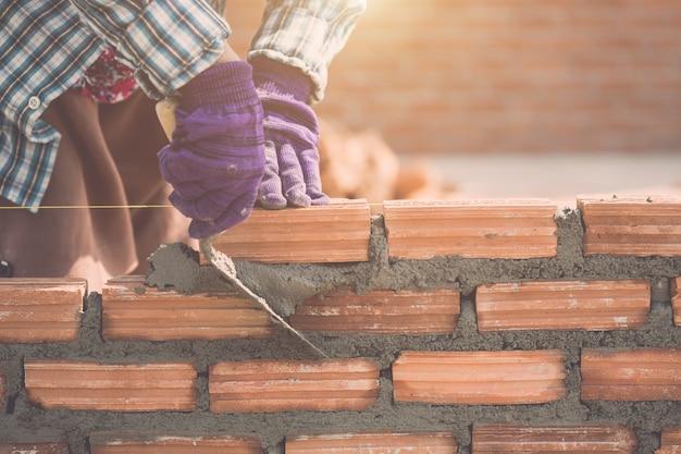 住宅建設の過程でレンガの壁を取り付ける労働者