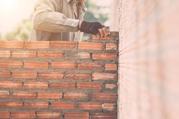 Рабочий устанавливает кирпичную стену в процессе строительства дома
